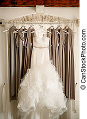 Long bridesmaid dress with a fluffy skirt on the eaves with bridesmaid dresses against the background of the window.