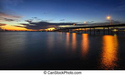 Long bridge to the sea at dusk