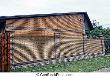 long brown fence of brick  in green grass