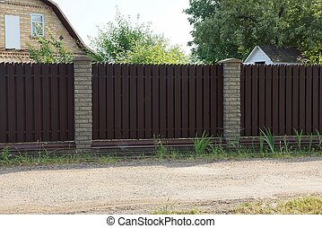 long brown fence of wooden planks and bricks on the street