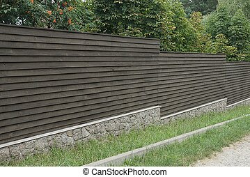 long brown gray fence wall on a stone foundation