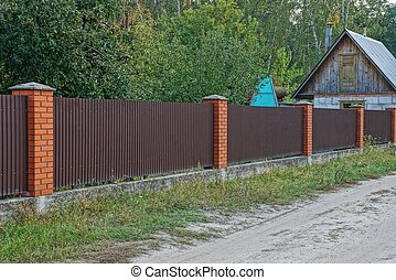 long brown metal and brick fence in the street by the road