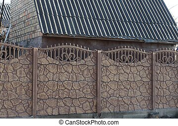 long brown stone wall of a fence on the street
