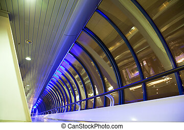 Long corridor with big windows in modern building at night, foreshortening from below