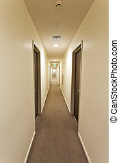 Long empty corridor in a hotel or apartment building interior with overhead lighting, doors on either side and illuminated exit sign