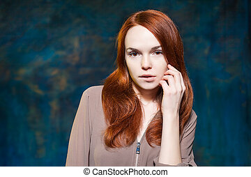 Long Curly Red Hair. Fashion Woman Portrait with Luxurious Hairstyle. Holiday Makeup. Bit her lips