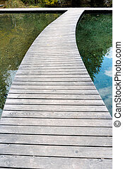 long curved wooden boardwalk and footpath over a blue mountain lake with reflections in the water