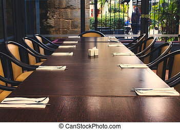 Long dining table with chairs in a restaurant