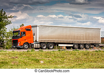Long-distance truck with a semitrailer moves in the countryside