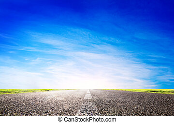 Long empty asphalt road, highway towards sun