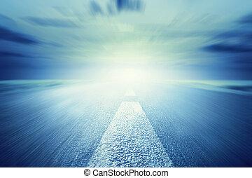 Long empty asphalt road towards light. Motion, speed, driving fast. Conceptual