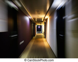 Long empty dark corridor with many doors in vintage style, toned. Motion blur effect