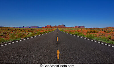 Long empty Road leading to Monument Valley landscape in Arizona USA
