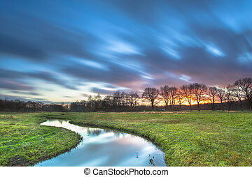 Long Exposue Sunset with Blurred Clouds over River Landscape
