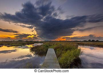 Long exposure image of a Wooden footbridge in wetland as a concept for challenge in nature reserve de Onlanden near Groningen, Netherlands