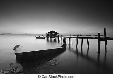 Long exposure image of old abandoned fisherman jetty in black and white.