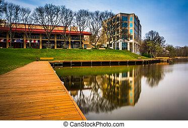 Long exposure of a walkway and buildings along the shore of Lake Kittamaqundi, in Columbia, Maryland.