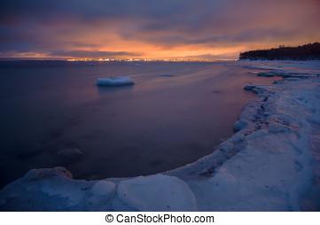Long exposure of dusk over frozen shoreline