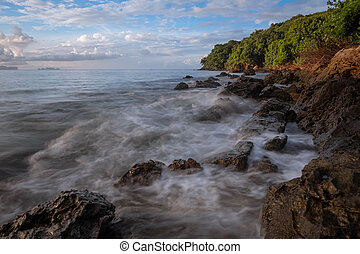 long exposure of sea waves lash line impact rock on the beach at morning time at Koh yao yai,Thailand