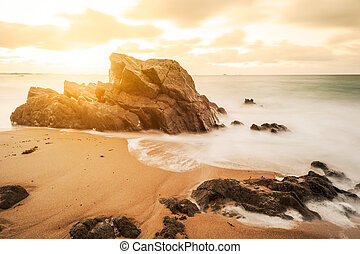 long exposure of sunset on a beach with rocks