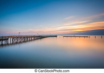 Long exposure of the pier and Chesapeake Bay at sunrise, in...