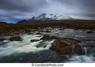 Long exposure of water over rocks and small waterfall on the River Sligachan on the Isle of Skye Scotland with the Cuillin mountain range in the distance with snow in winter, Isle of Skye, Scotland