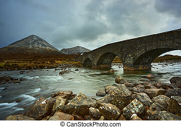 long exposure of water with rocks in the foreground in front of the river and the old bridge over the river Sligachan on the Isle of Skye Scotland with the Cuillin mountain range in the distance, Isle of Skye, Scotland