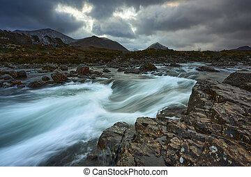 Long exposure of water with rocks in the foreground, winter vegetation on the River Sligachan on the Isle of Skye Scotland with the Cuillin mountain range in the distance, Isle of Skye, Scotland