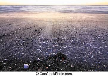Long exposure of waves flowing over rocks at sunset on Hokitika Beach on the west coast of New Zealand's south island.