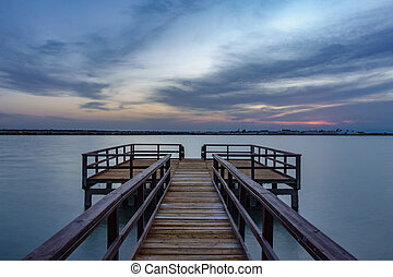 Long exposure of wooden pier at sunrise