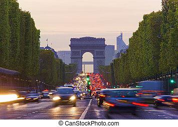 Long exposure photo of street traffic near Arc de Triomphe, Champs Elysees boulevard. Paris, France