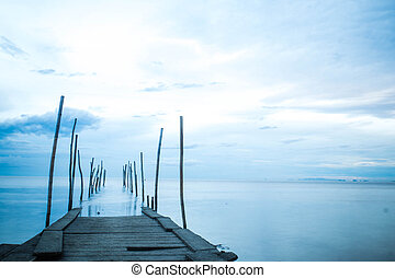 Long exposure photograph of wooden bridge in blue sea