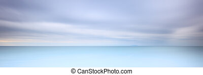 Long exposure photography panorama 3:1 with soft sea and cloudy sky. 2 minutes time exposure.