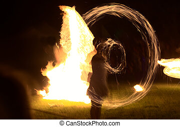 Long exposure shot of moving burning torches and fire with vague silhouette of a person