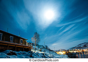 Long Exposure Shot of Night Sky with a Winter Snow Covered Landscape with Houses and Water in Norway. This place is located at Norwegian fjords at Ersfjordbotn.