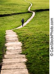Long Flagstone Path Through Field - Woman walking on a long...
