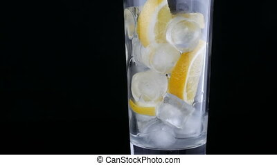 Long glass with lemon slices and ice cubes on a black background.