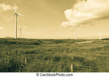 long grass and bogland with wind turbines in sepia