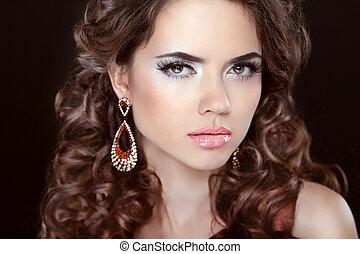 Long hair. Beautiful brunette girl model with fashion earrings.