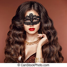 Long hair. Beautiful young woman in black mysterious venetian mask. Makeup. Wavy hairstyle. Fashion golden jewelry. Studio portrait.