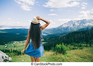 long hair woman travel in mountains landscape back view