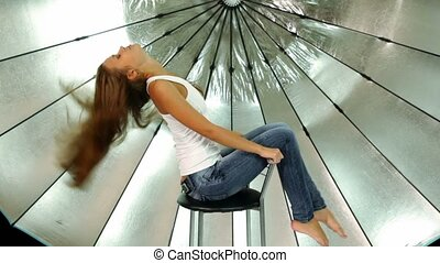 Long hair young girl sits on chair in front of reflector in photo studio