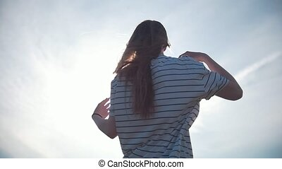 Long hair young woman flying in the wind at sunset, slow...