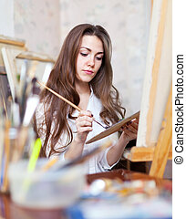 Long-haired artist paints on canvas in workshop