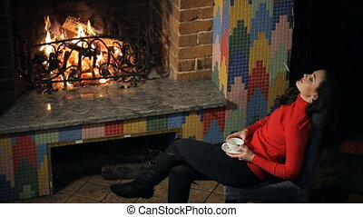 Long-haired beauty has a rest by drinking tea near burning...