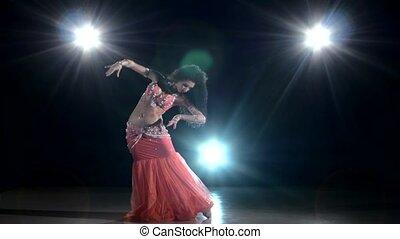 Long-haired belly dancer girl dancing exotic dance movement on black, back light