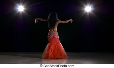 Long-haired belly dancer girl dancing exotic dance movement on black, back light, slow motion