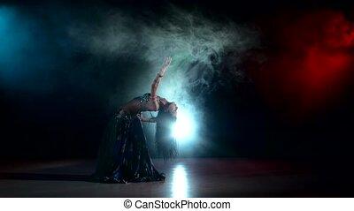 Long-haired belly dancer girl dancing exotic dance movement on black, smoke, back light