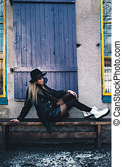 Long haired blond woman wearing a black fedora hat, a black coat with woollen lapels, and white boots, sitting on a wooden bench behind blue window shutters