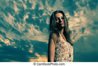 Long haired blonde against cloudy sky